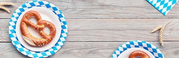 Oktoberfest, apartamento leigos na mesa de madeira rústica com orelhas de pretzel e trigo, composição de banner