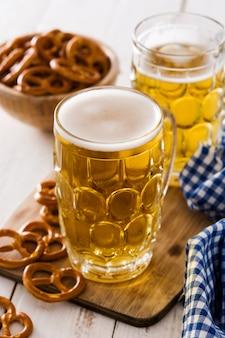 Oktoberfest cerveja e pretzel na mesa de madeira branca