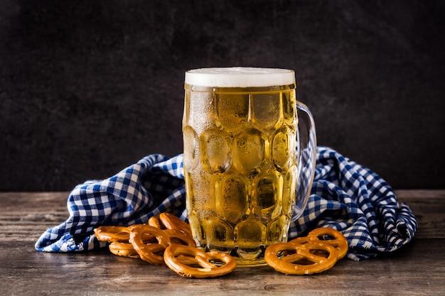 Oktoberfest cerveja e pretzel na mesa de madeira.