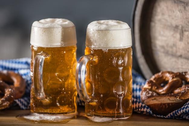 Oktoberfest dois cerveja grande com barril de madeira pretzel e toalha de mesa azul.