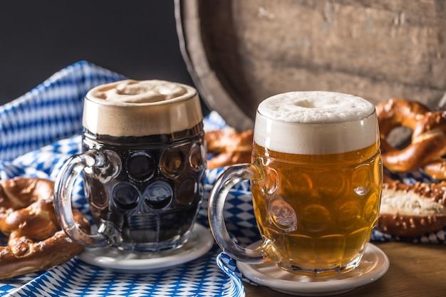 Oktoberfest duas cervejas com barril de madeira pretzel e toalha de mesa azul.