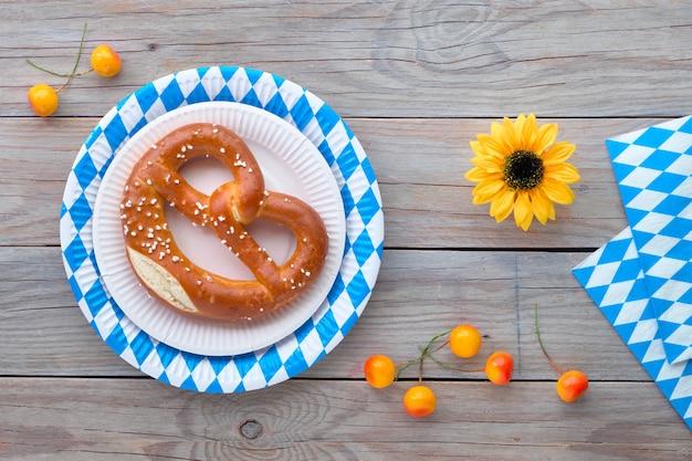Oktoberfest, pretzel no prato descartável azul e branco, bandeiras decorativas e decorações de outono