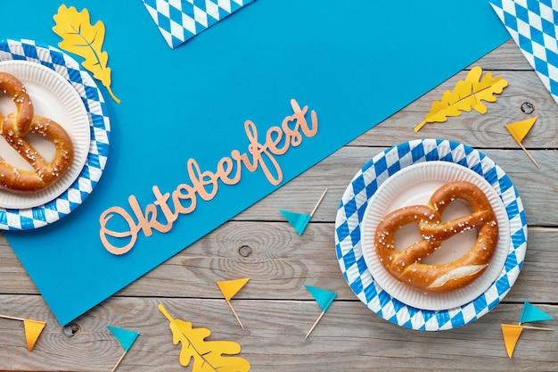 Oktoberfest rústico com prezels em pratos de papel, bandeiras de papel e folhas de outono