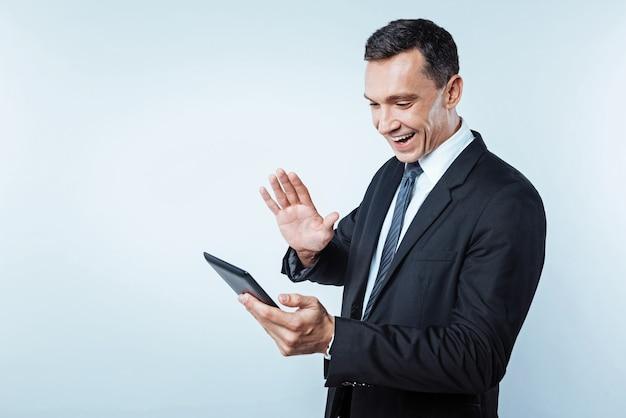 Olá. cintura para cima foto de um empresário maduro radiante renunciando a alguém enquanto focaliza sua atenção em uma tela de um computador tablet durante uma conversa de videochamada.