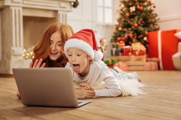 Olá. família extremamente feliz deitada no tapete fofo e fazendo caretas engraçadas enquanto conversa durante uma videochamada.