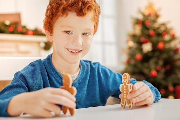 Olá. garoto ruivo radiante, sentado à mesa e curtindo brincar com um homem-biscoito de gengibre em casa.