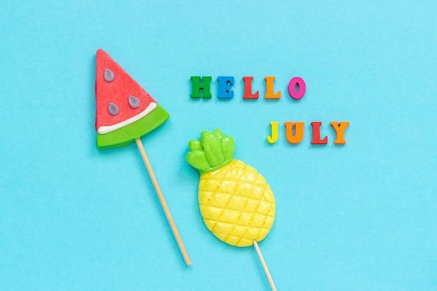 Olá julho colorido texto, abacaxi e melancia pirulitos na vara