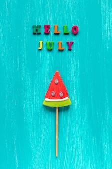 Olá julho, pirulito de melancia sobre fundo azul de madeira.
