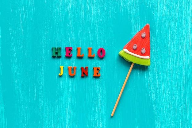 Olá junho e pirulito de melancia sobre fundo azul de madeira.