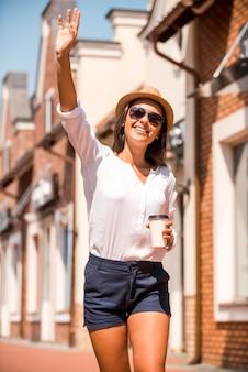Olá! mulher jovem e bonita com chapéu e óculos escuros acenando para alguém e sorrindo enquanto caminhava pela rua