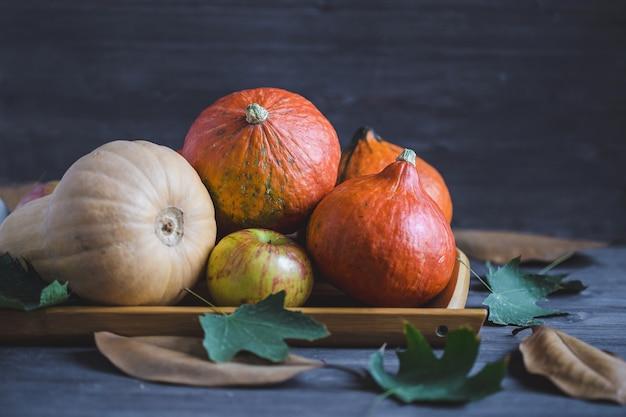 Olá outono. abóboras alaranjadas maçãs folhagem de outono em um fundo de madeira