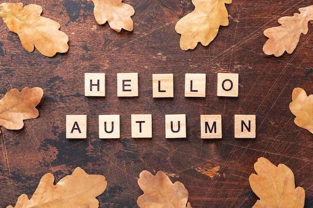 Olá palavras outono e carvalho seco deixa na mesa de madeira
