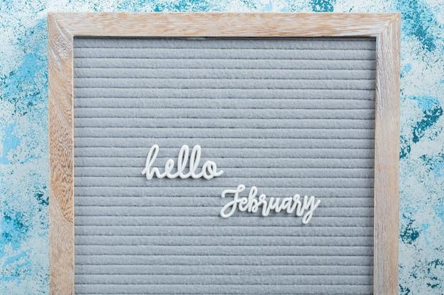 Olá pôster de fevereiro na superfície azul