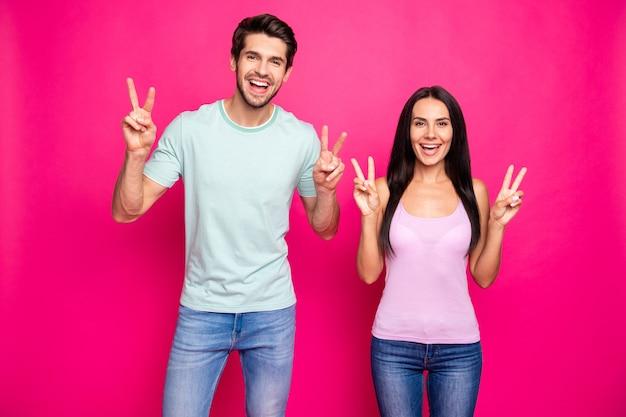 Ola queridos amigos! foto de um casal engraçado, levantando as mãos, mostrando os símbolos do sinal-v, vestindo roupas casuais isoladas de fundo de cor rosa