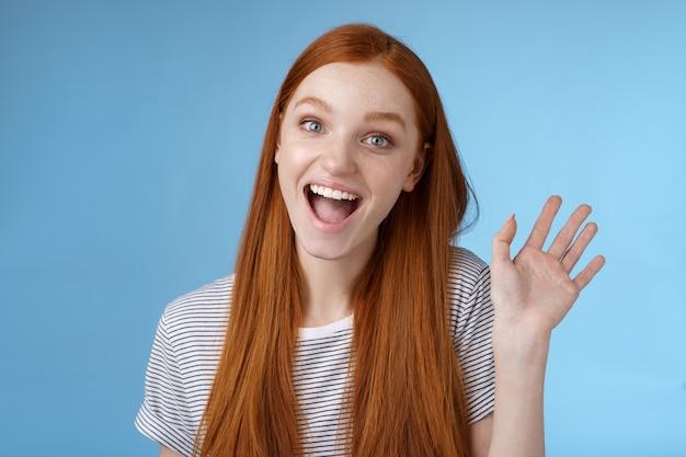 Olá quero ser amigos. entusiasta ruiva fofa novato feminino conhecendo colegas de trabalho sorrindo feliz acenando com a mão levantada oi gesto de saudação de boas-vindas, diga tchau em pé fundo azul.