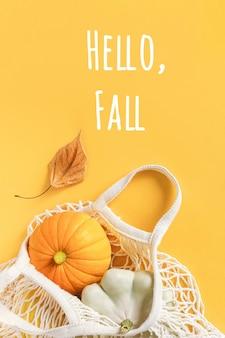 Olá, texto de outono e composição de outono feita abóbora colheita de vegetais cabaças, abóbora pattypan no saco de malha de compras, folha de outono em fundo laranja. conceito bem-vindo outono vista superior flat lay.