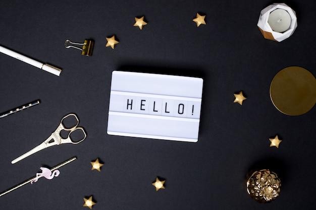 Olá texto em uma mesa preta com estrelas douradas