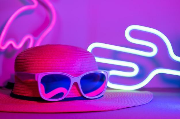 Olá verão com chapéu e óculos de sol reflexão flamingo luz de néon com cactos na luz rosa e azul