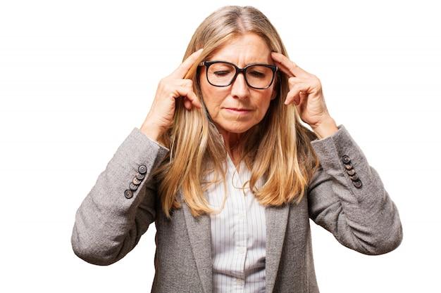 Old mulher com óculos para ver e dedos nas têmporas