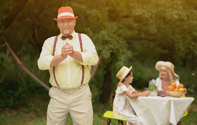 Oldman elegante com pote ao ar livre mostra o polegar para cima o sinal