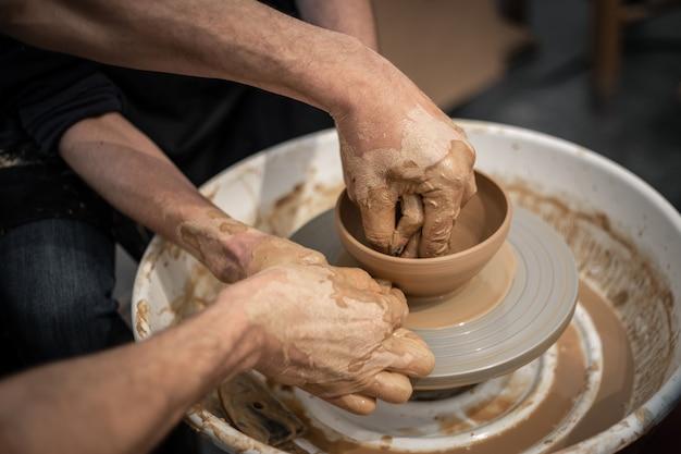Oleiro especialista ensina um homem a trabalhar na roda de oleiro