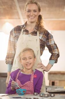 Oleiro feminino, ajudando a garota na pintura na oficina de cerâmica