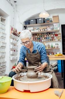 Oleiro feminino sênior, trabalhando na roda de oleiro enquanto está sentado em sua oficina