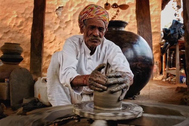 Oleiro indiano no trabalho. artesanato de shilpagram, udaipur, rajastão, índia