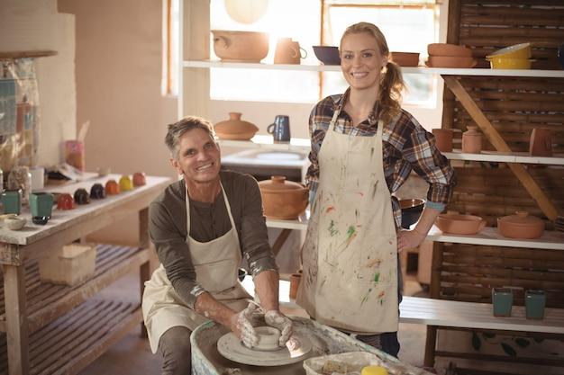 Oleiro masculino, ajudando o oleiro feminino na oficina de cerâmica