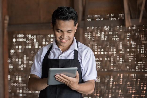 Oleiro masculino usando tablet digital na oficina de cerâmica