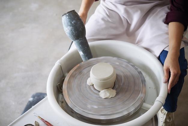Oleiro secando fundo de panela de barro na roda de oleiro com ventilador elétrico