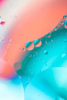 Óleo colorido abstrato cai no líquido no fundo desfocado em tons