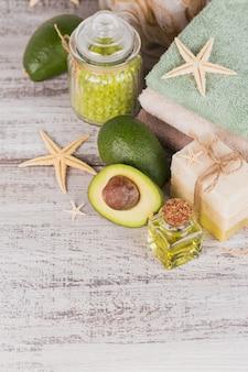 Óleo cosmético natural e sabonete artesanal natural com abacate em fundo branco de madeira rústico. cuidados com a pele, rosto e corpo saudáveis. conceito de spa e sauna.