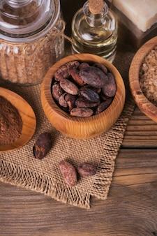 Óleo cosmético natural, sal marinho e sabonete artesanal natural com grãos de cacau em fundo de madeira rústico. cuidados com a pele saudável. conceito de spa.