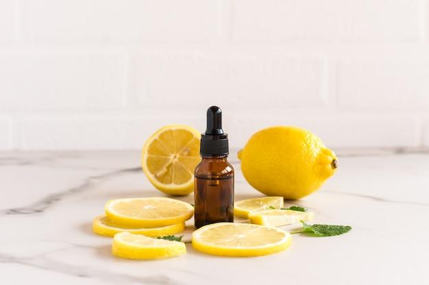 Óleo cosmético ou essencial de limão em uma garrafa de gotejamento no fundo de frutas maduras de limão e parede de tijolo branco. um conceito natural de autocuidado.