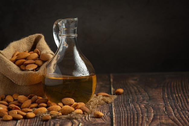 Óleo de amêndoa em garrafa em fundo de madeira escura Foto gratuita