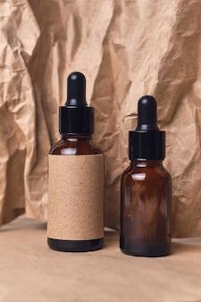 Óleo de aroma natural em dois frascos conta-gotas de vidro âmbar em papel amassado. design de embalagem de produtos de beleza orgânicos