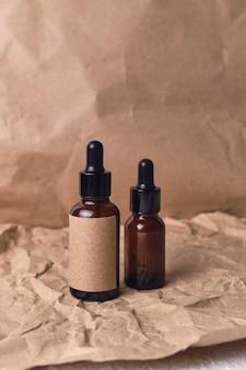 Óleo de aroma natural em um frasco conta-gotas de vidro âmbar marrom em papel amassado. design de embalagem de produtos de beleza orgânicos