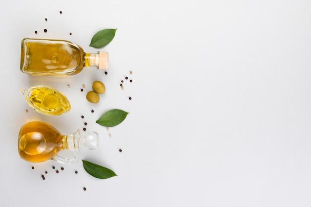 Óleo de azeitonas em garrafas e copo com folhas e azeitonas próximo