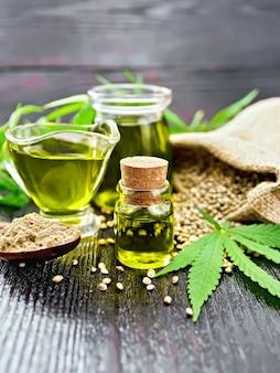 Óleo de cânhamo em dois potes de vidro e molheira com grãos em um saco, uma colher com farinha, folhas e talos de cannabis