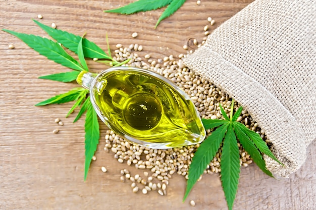 Óleo de cânhamo em uma molheira de vidro com grãos em um saco, folhas e talos de cannabis no fundo de uma velha placa de madeira vista de cima