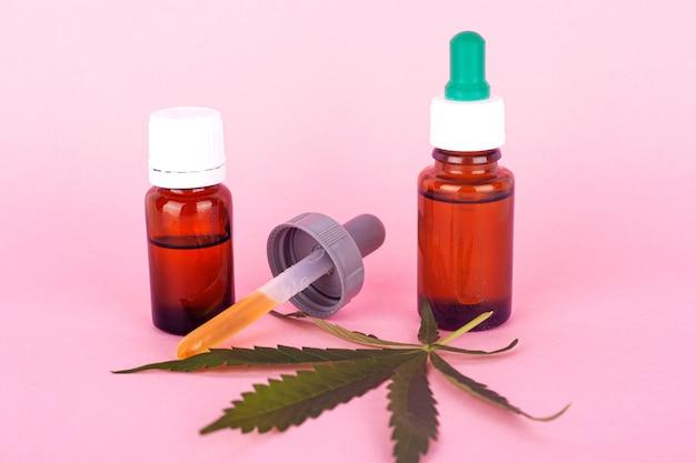 Óleo de cânhamo para uso médico, garrafas com extrato de maconha medicinal em close-up de fundo rosa.