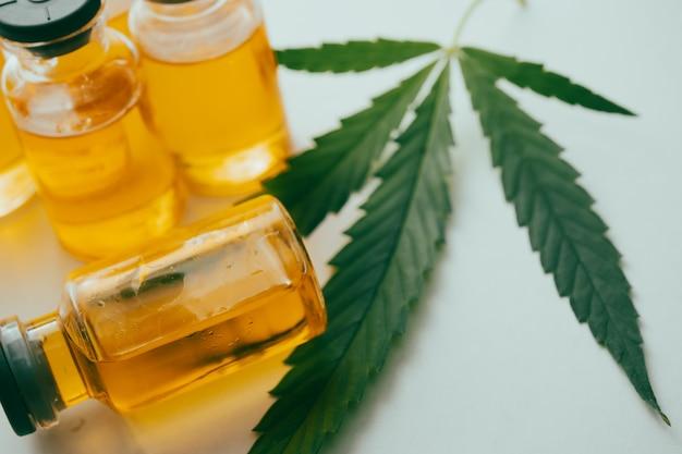 Óleo de cannabis em frascos com uma folha verde sobre fundo branco. conceito de medicina alternativa.
