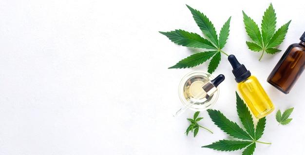 Óleo de cannabis em óleo de cânhamo de garrafa e folhas de cannabis em fundo branco. vista superior, copie o espaço. bandeira