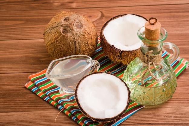 Óleo de coco e leite e coco em uma mesa de madeira