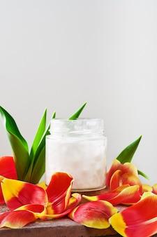 Óleo de coco em um frasco em branco cercado por pétalas de tulipa, close-up com espaço de cópia