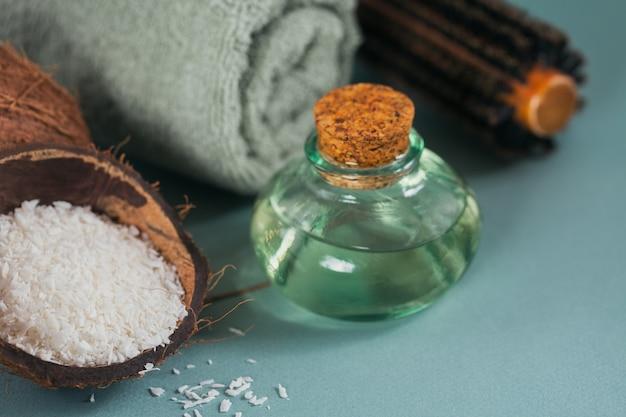 Óleo de coco em uma garrafa com coco, toalha e escova de cabelo em fundo azul claro
