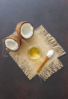 Óleo de coco em uma jarra e cocos frescos em uma mesa escura. cosméticos naturais.
