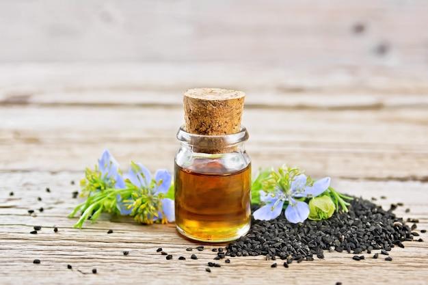Óleo de cominho preto na garrafa, sementes e galhos de sementes com flores azuis e folhas de kalingi a bordo
