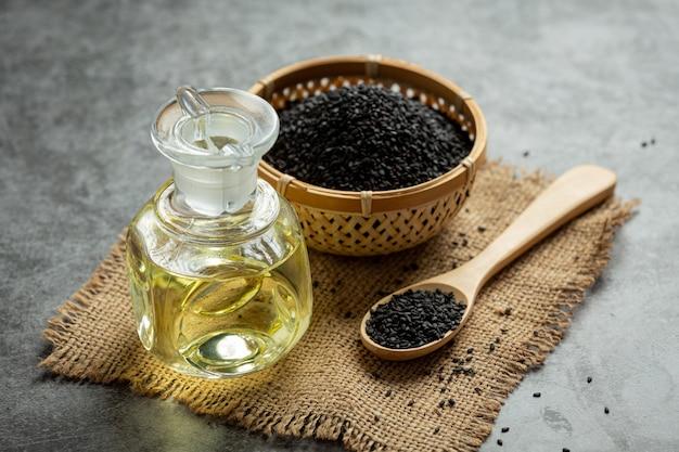 Óleo de gergelim e sementes de gergelim pretas cruas em fundo escuro